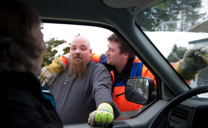 Bildet er tatt innenfra en bil. I åpningen til vinduet ser vi to arbeidskarer somhar armene rundt hverandre.
