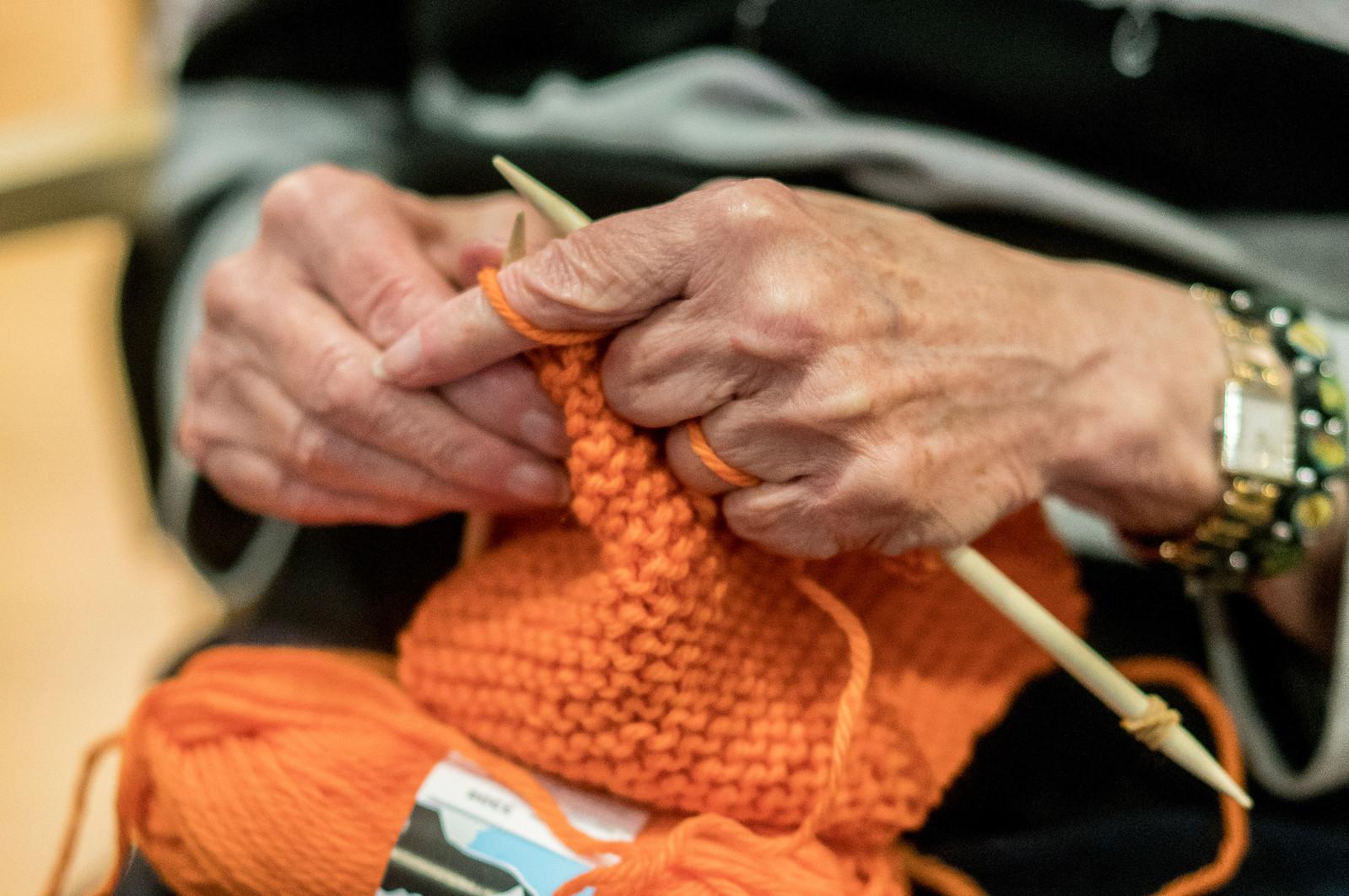 Hender som strikker et oransje skjerf