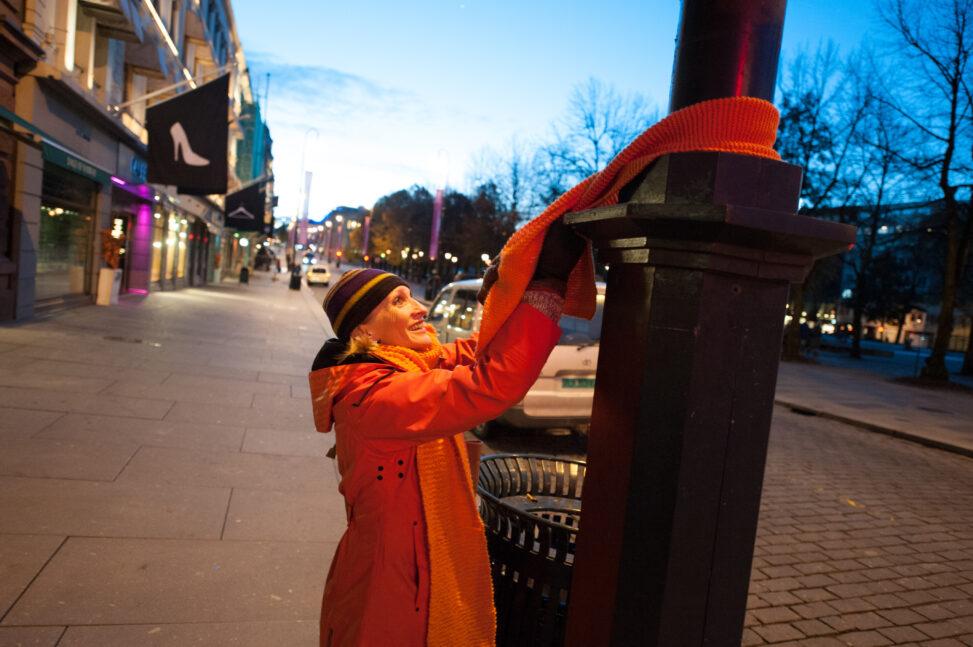 Bilde av kvinne som henger opp oransje skjerf på en trestamme langs Karl Johan i Oslo.