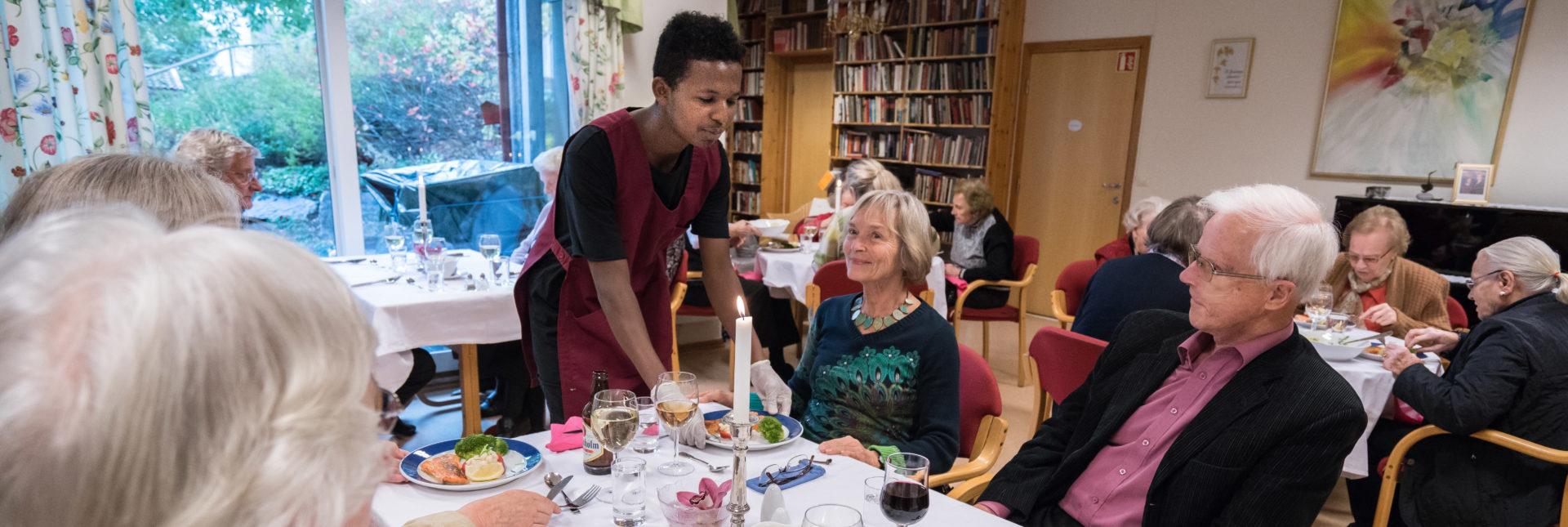 en mindreårig asylsøker serverer gjester på St.hansheugen seniorsenter til god stemning. Bilde