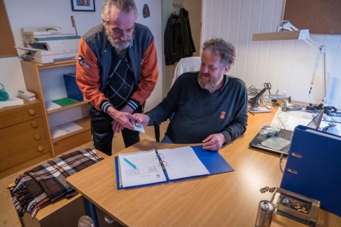Bildet viser en mann som blir gitt en to hundrelapp av en annen mann. Foran dem ligger en perm med ark med signaturer og avkrysning for hvem som har deltatt på Lønn som fortjent i dag.