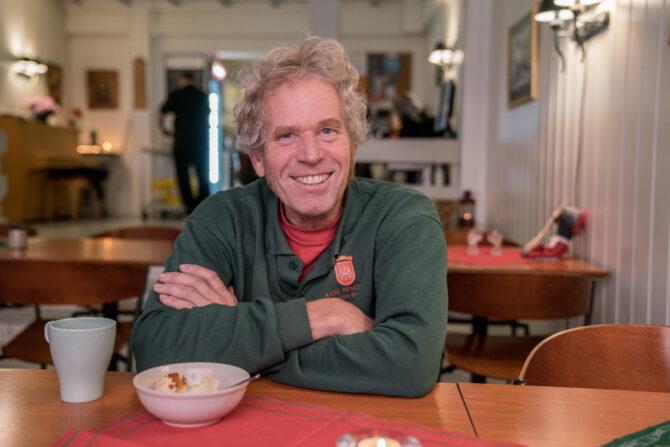 Bildet viser en mann som sitter med armene i kors lent på et bord og smiler bredt. Foran seg har han en skål med dessert.