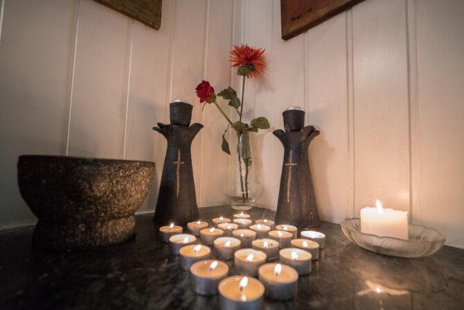 Bildet viser et hjørne med en steinplate der det står plassert flere telys som er tent. Bak telysene står to lysestaker med korsmotiv på og en blomst i en vase.