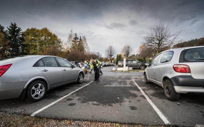 Bildet viser en mann i gul refleksvest som står i en åpen parkeringsluke mellom to biler på en parkeringsplass og plukker søppel med en lang søppelplukkerklype.