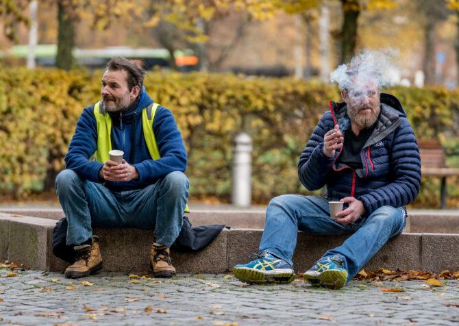 Bildet viser to menn som sitter på kanten av en tørrlagt fontene på høsten. Mannen til venstre har blå genser og gul refleksvest på seg. Han ser ut mot venstre i bildet. Mannen til høyre har blå boblejakke og sitter og tar seg en røyk mens han ser ut mot høyre av bildet.