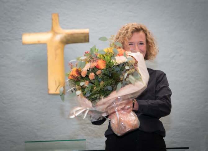 Bildet viser Kari Veiteberg med en stor blomsterbukett foran seg. Ansiktet hennes er halvveis skjult av blomstene. På veggen bak henne henger det et stort kors i gull