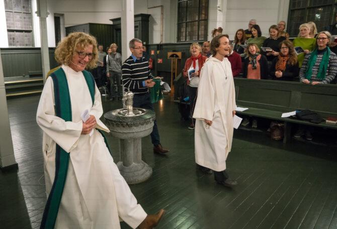 Bildet er fra kirkerommet i andre etasje i Tøyenkirken i Oslo. Kari Veiteberg (foran i bildet) går i hvit prestekjole sammen med to andre gjennom kirkerommet. I bakgrunnen sees kirkegjengere i benkeradene som står og synger med.