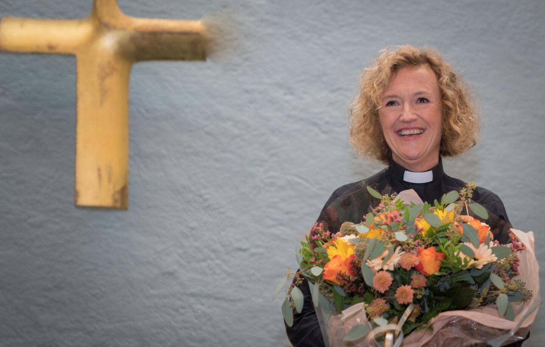 Bildet viser Kari Veiteberg stående med en stor blomsterbukett i armene. Hun smiler bredt og har på seg en svart skjorte med prestekrage. Bak henne på veggen til venstre henger et stort kors i gull.
