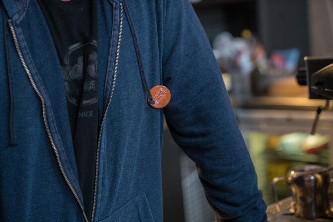 """Nærbilde av buttonen """"Ingen er bare det du ser"""", plassert på en blå genser. Ordene er Kirkens Bymisjon sitt slagord og buttonen har fargen oransje."""