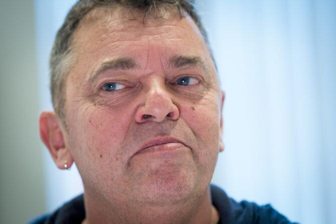 Bildet viser et nærbilde av Trond Henriksen med et litt ubestemmelig uttrykk. Han ser ut til venstre for bildet med ansiktet vendt mot kameraet. Han har en ring i øret, kort hår, blå øyne og blå genser.