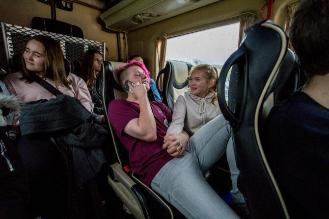 Bilde av fire ungdommer i baksetet på en minibuss. En av dem snakker i telefonen, mens de andre ser ut av vinduet.