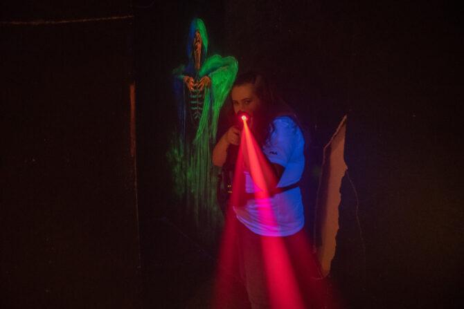 Bildet viser en jente med konsentrert blikk i et mørkt rom som holder en pistol med en rød laserstråle foran seg. I bakgrunnen er det en mørk vegg med et bilde av et skjelett med en grønn kappe.