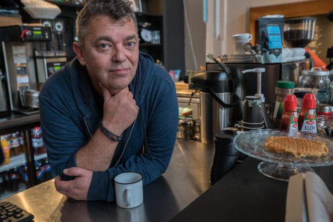 Portrettbilde av Trond Henriksen. Trond Henriksen ser mot kameraet mens han holder hånden under haka og lener seg over disken på en kafé. Foran seg har han en kaffekopp.