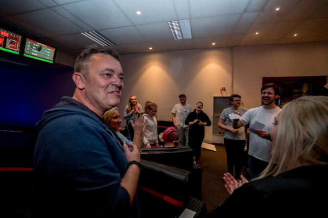 Bildet viser Trond Henriksen til venstre i bildet foran som smiler. Bak ser man skjermer og stoler i en bowlinghall, med en gjeng med mennesker som ler og smiler og ser mot Trond Henriksen. De leser opp og deler ut resultater fra bowlingen.