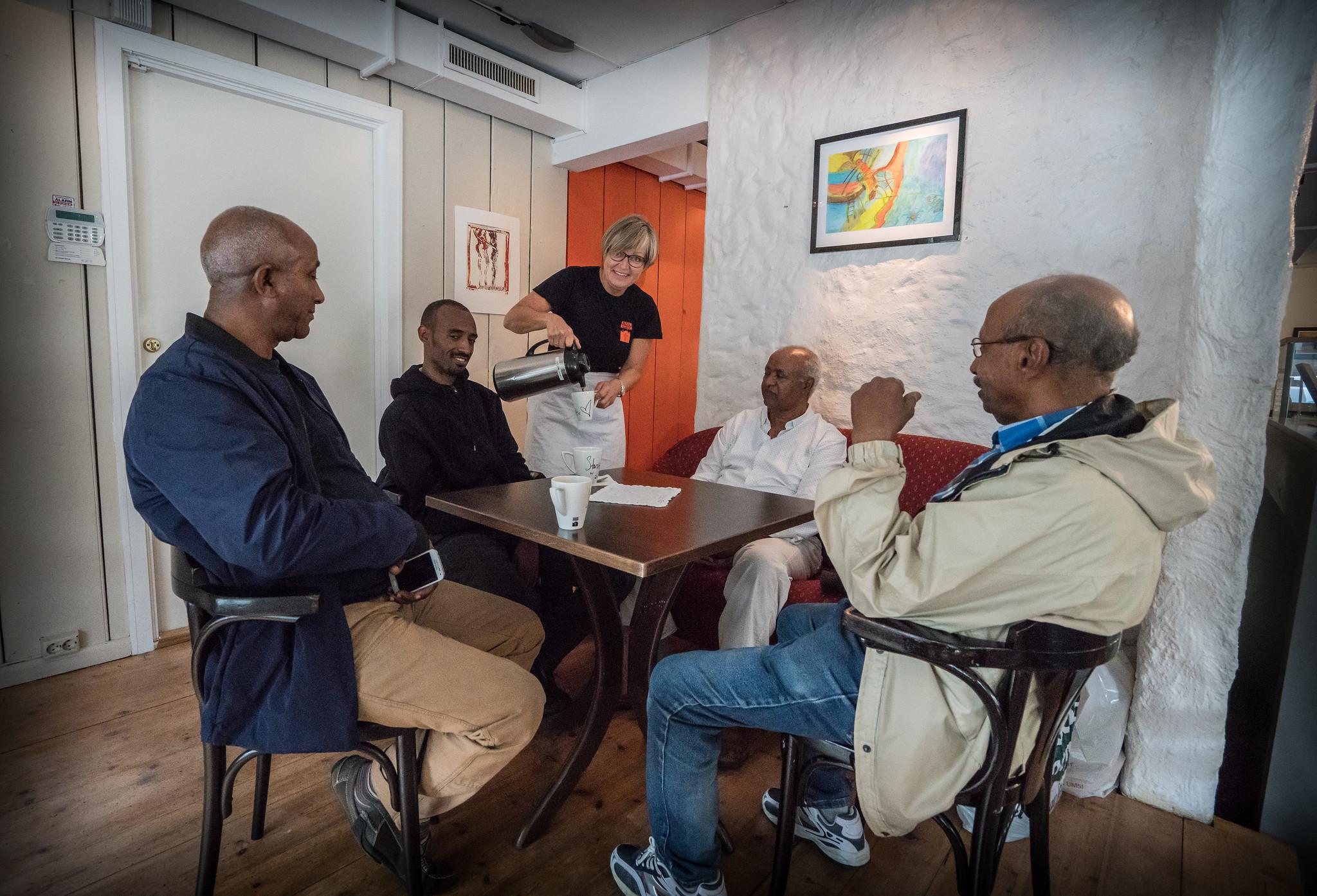 Bildet viser fire menn som sitter rundt et bord. En dame står bak bordet i midten av bildet og smiler mens hun skjenker kaffe i kaffekopper. At de står her er en av flere resultater av pengene Kirkens Bymisjon samlet inn under tv-aksjonen 2004.