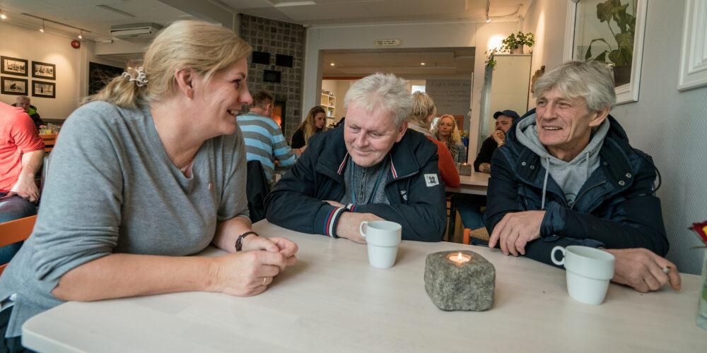 Bildet viser tre mennesker som sitter ved et bord og smiler til hverandre. De sitter på Kirkens Bymisjons kafé i Tønsberg. Her har kokkken Siv Johansen (t.v.) utviklet et nytt take away-tilbud om julemiddag. i Tønsberg. Nå spiser færre Grandiosa.