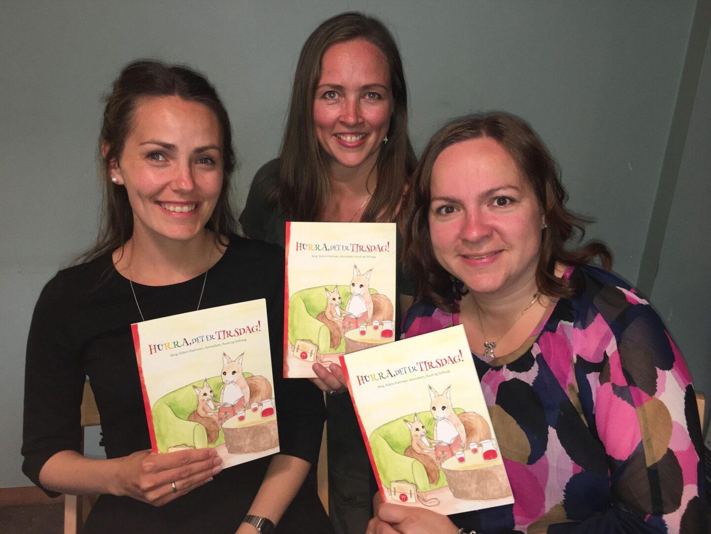 Tre koordinatorer fra Home-Start med barneboka «Hurra, det er tirsdag!» i hånda.