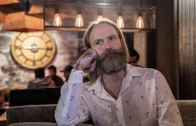 Adam Schjølberg ser tankefull ut på en kafe. Han har på seg hvit skjorte med bittesmå svarte palmer.