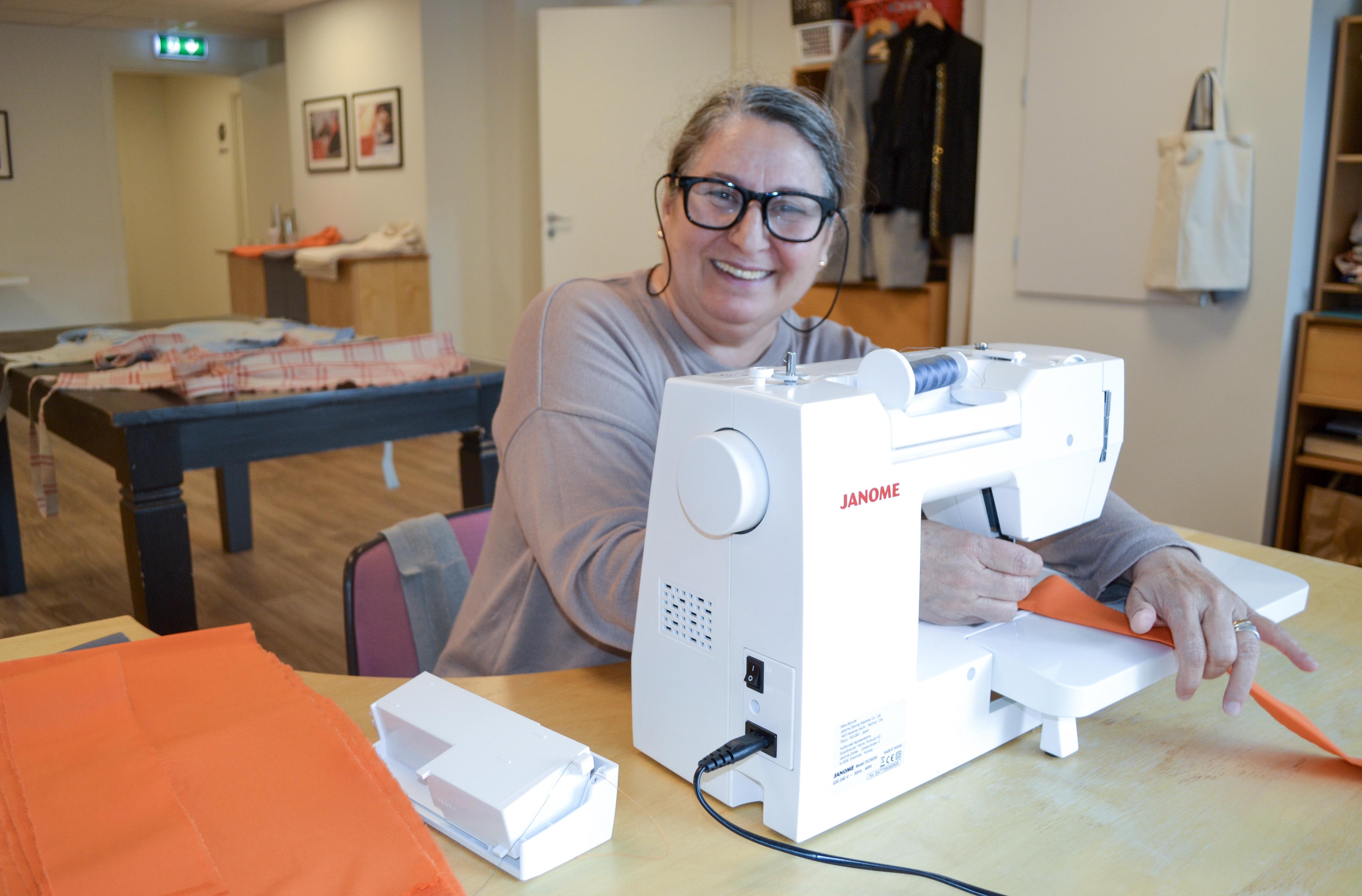 Nachmie har på seg runde briller og smiler. Hun sitter bak en hvit symaskin.