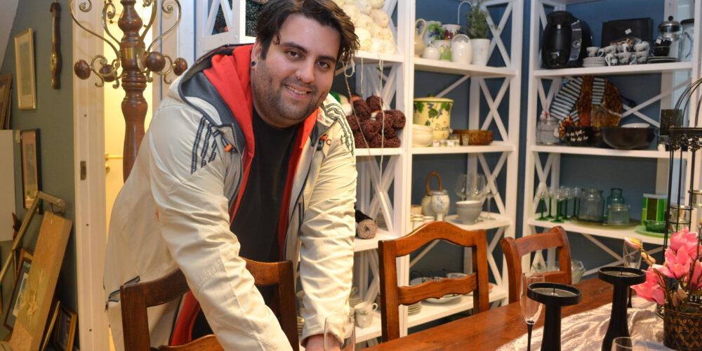 Åmid står bak et bord i butikken og gjør i stand en utstilling med varer.
