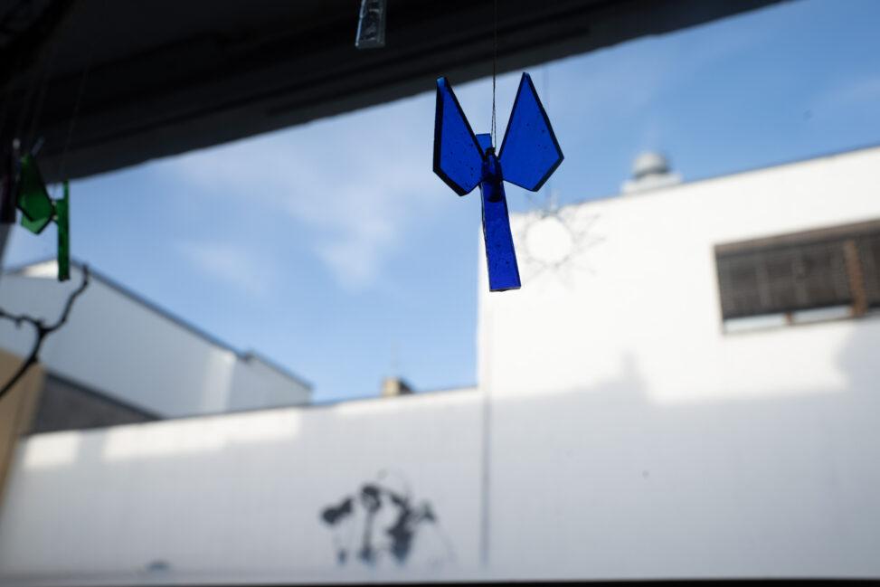 En blå engel laget på Englefabrikken i Bodø henger i vinduskarmen