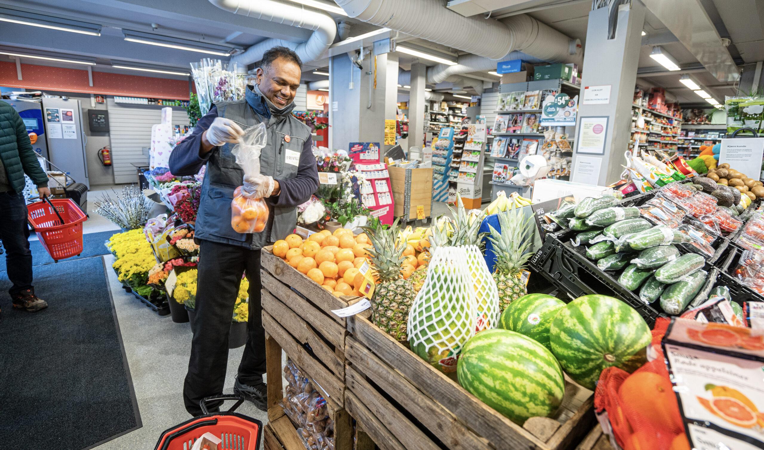 Handlehjelp Hemal er i butikken og i ferd med å finne fram appelsiner som står på handlelista