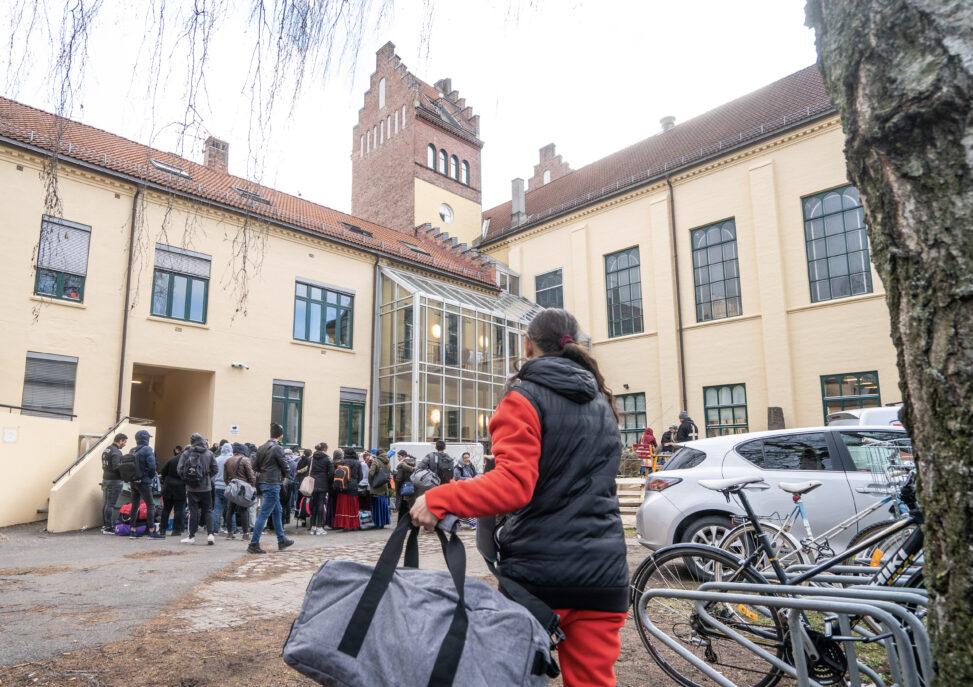 Tilreisende fra Romania på vei ut til bussen som skal ta dem til Gardermoen og videre hjem etter korona-utbruddet