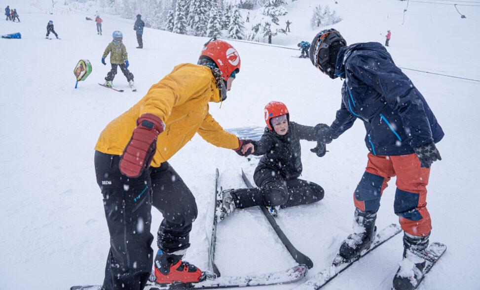 To stykker hjelper en annen opp som har falt på ski