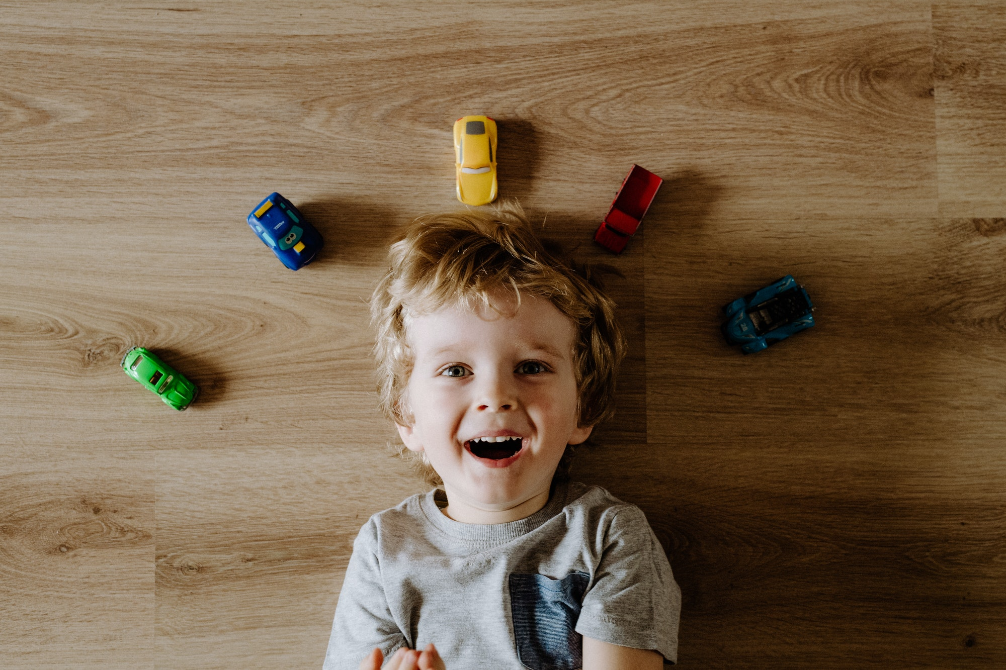 A top view of a toddler boy with toy cars lying on floor at home