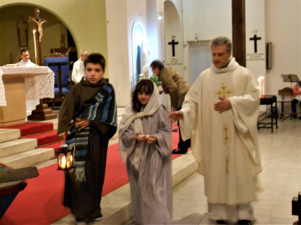 Guidé par la lanterne de Joseph, Marie va confier l'enfant Jésus à l'abbé Jean-Marc pour le coucher dans la crèche