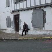 Frère Alexis sur le banc de pierre du presbytère ou s'était assis le saint