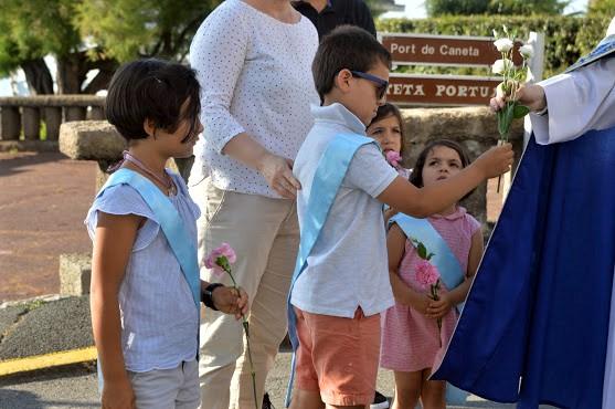 L'abbé Jean-Marc distribue les fleurs aux enfants