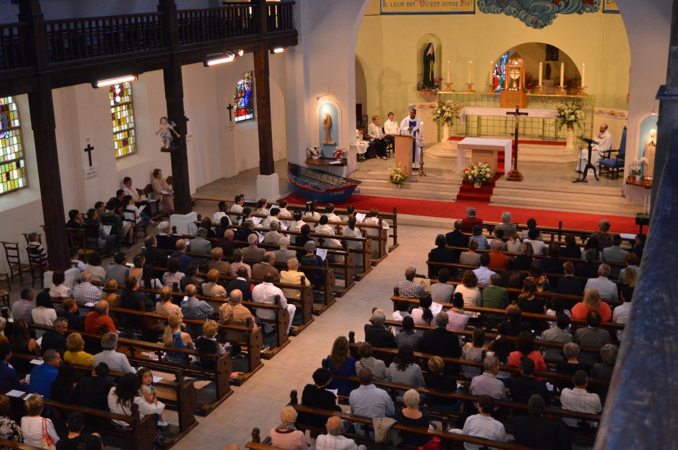 ... ainsi que l'assemblée, à l'écoute du célébrant, l'abbe Roger Makaya
