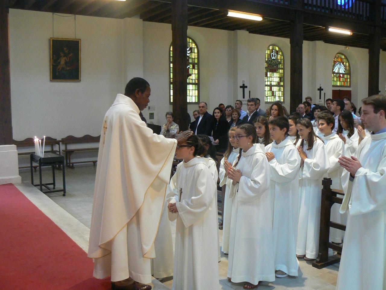 L'abbé Roger bénit les enfants avant la communion