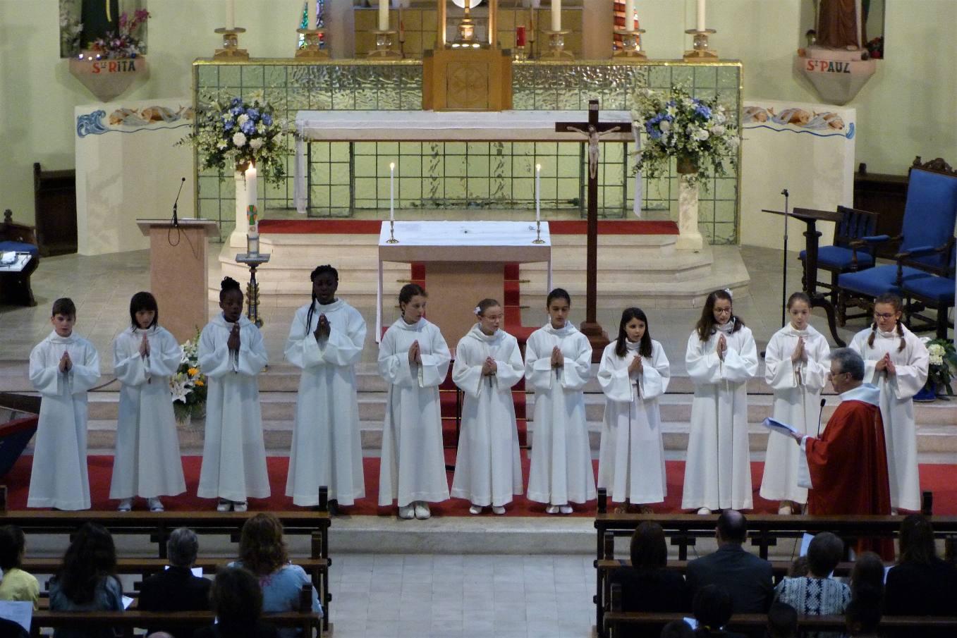 Le vêtement blanc, la Croix ; maintenant, l'abbé les invite à renouveler le signe de l'eau de leur baptême