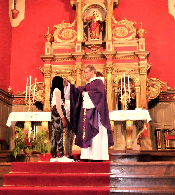 L'abbé Jean-Marc Lavigne trace le signe de Croix sur le front des deux sœurs...
