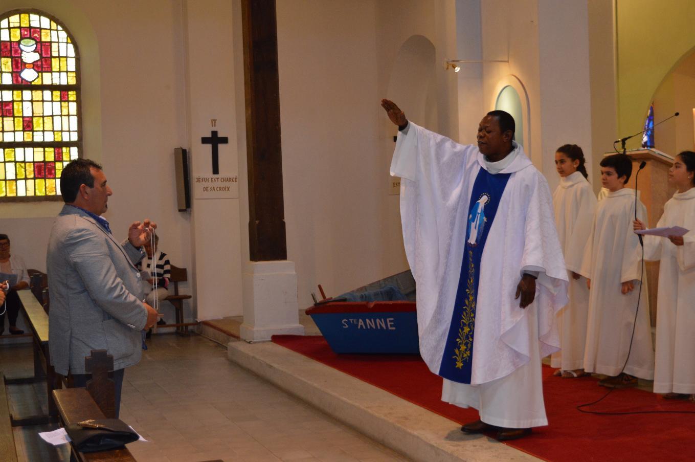L'abbé Roger bénit les Croix qu'un parent passera au cou de son enfant
