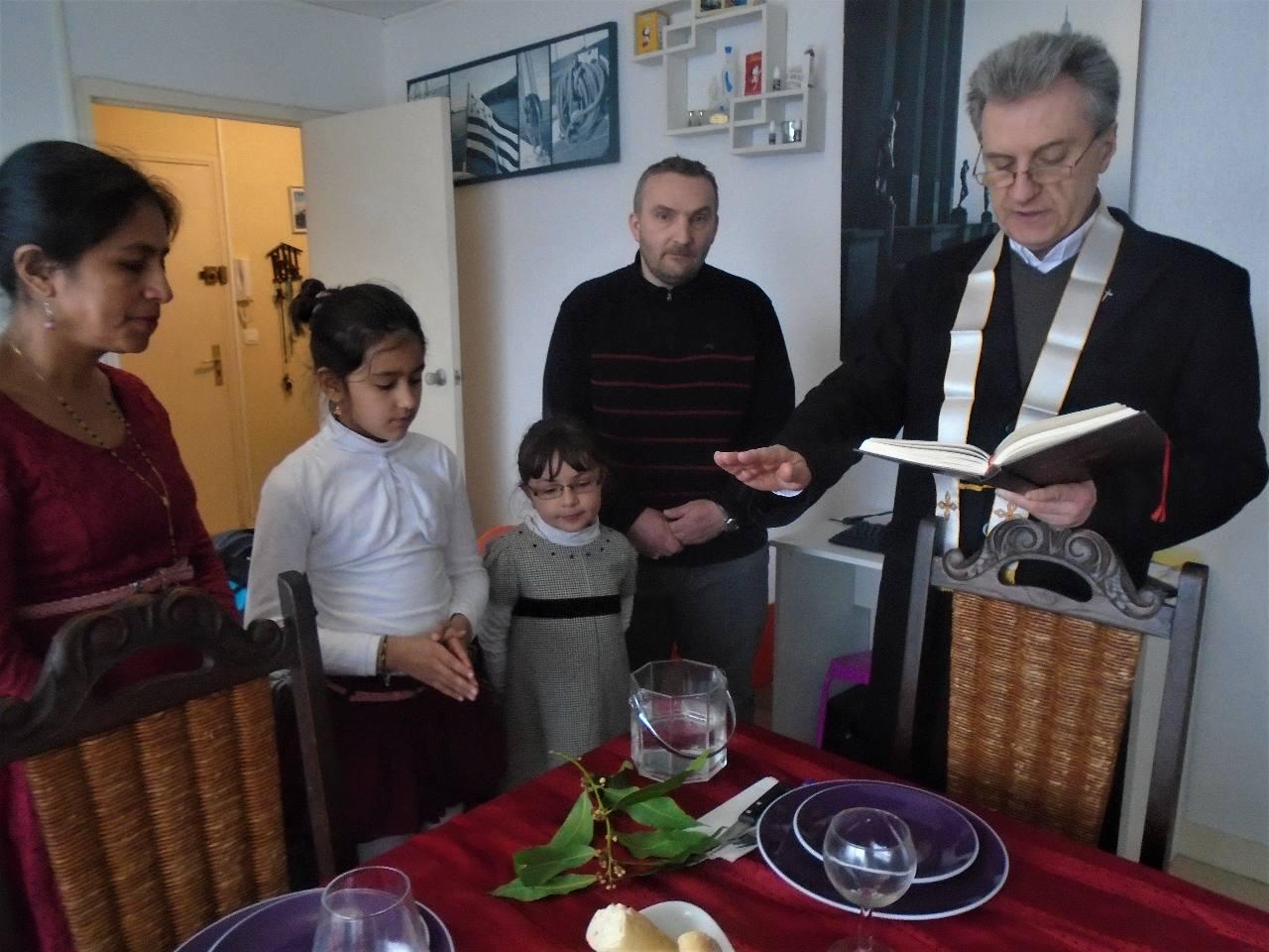L'abbé Jean-Marc bénit l'eau (Evy, mère de famille, la gardera respectueusement pour la prière journalière de la famille)