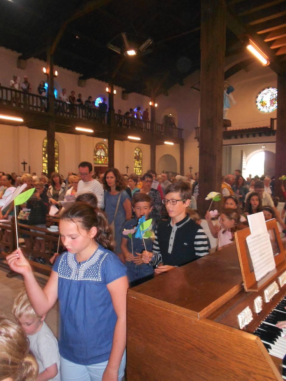 """Les enfants lèvent leur fleur en chantant """"Ave Maria"""""""