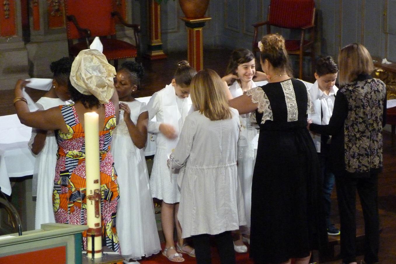 Les marraines revêtent leur filleul(e) du linge blanc, à leur prénom et  brodé des signes de l'Eucharistie. Ils ont revêtu le Christ