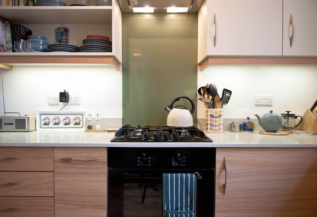 new L-shaped kitchen with flat panelled doors and glass hob splashback