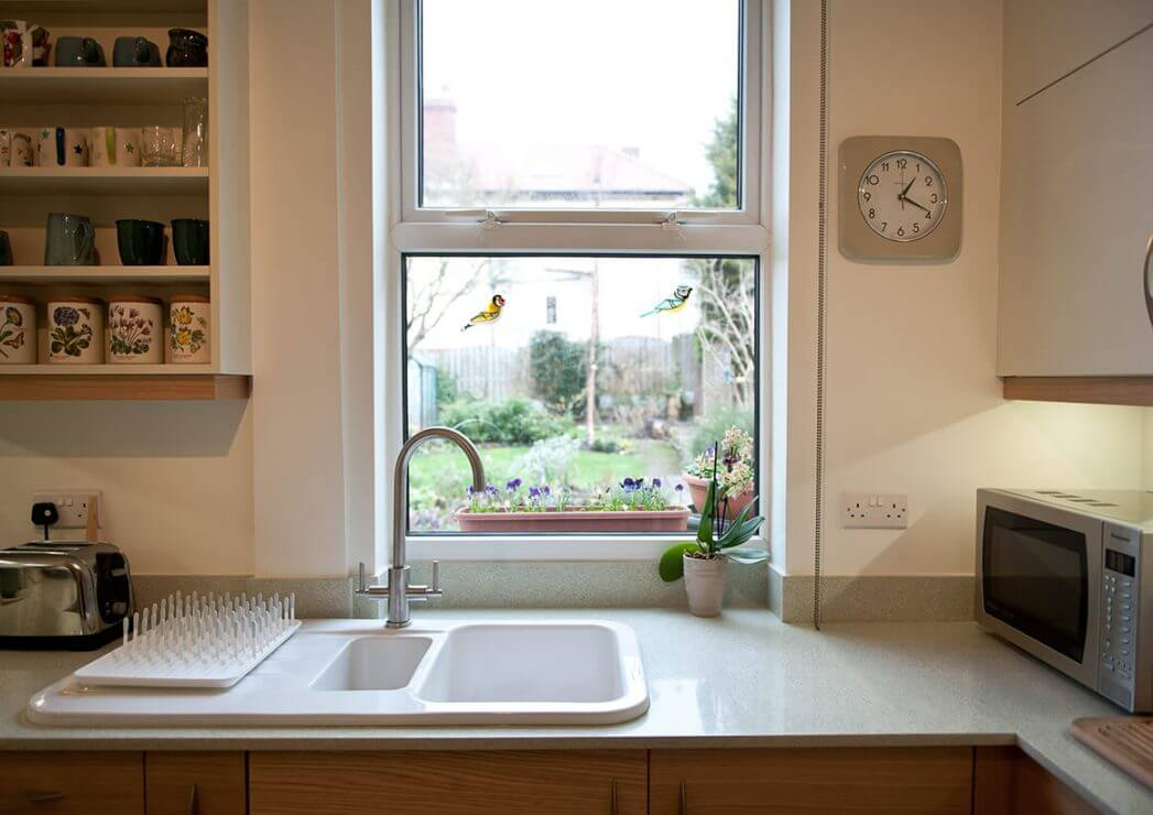 new L-shaped kitchen with flat panelled doors and ceramic kitchen sink