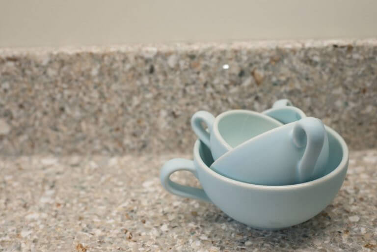 pale blue Nigella measuring cups on recycled glass kitchen worktop