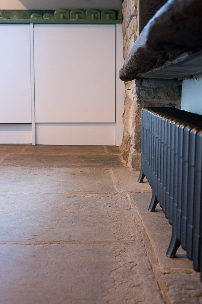 stone flags on kitchen floor and kitchen cabinets scribed to stone kitchen wall