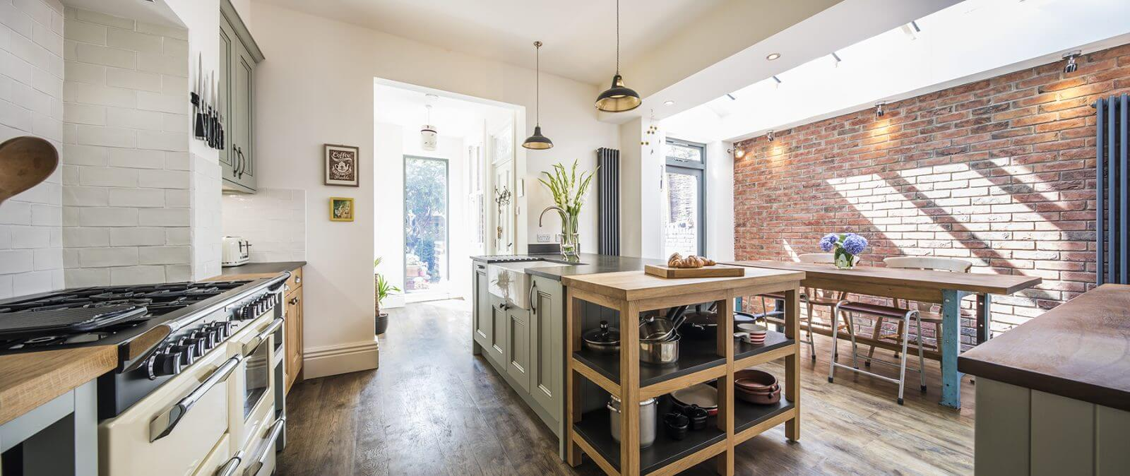 large victorian kitchen extenstion with large kitchen island and solid timber kitchen units and exposed brick wall