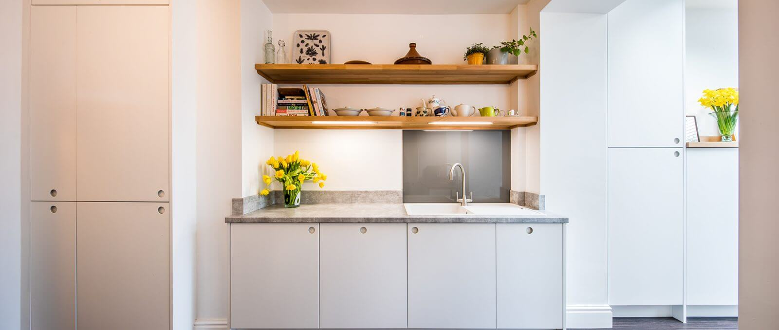 scandi new kitchen with white cabinet doors and circular cutout pull handles and open shelving