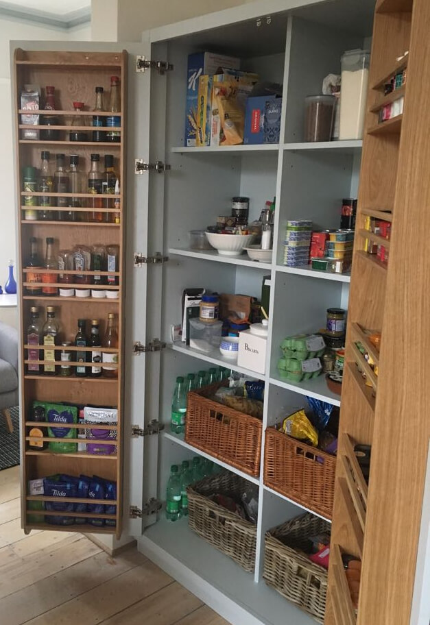full heigth bespoke kitchen larder with doors open to show fully stocked food cupboard and cooking supplies