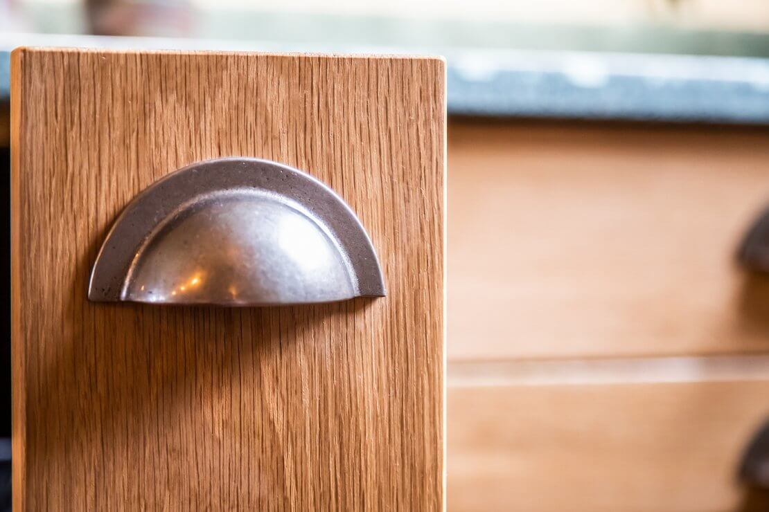 cup handle in bespoke new large u-shaped kitchen with handmade solid oak doors