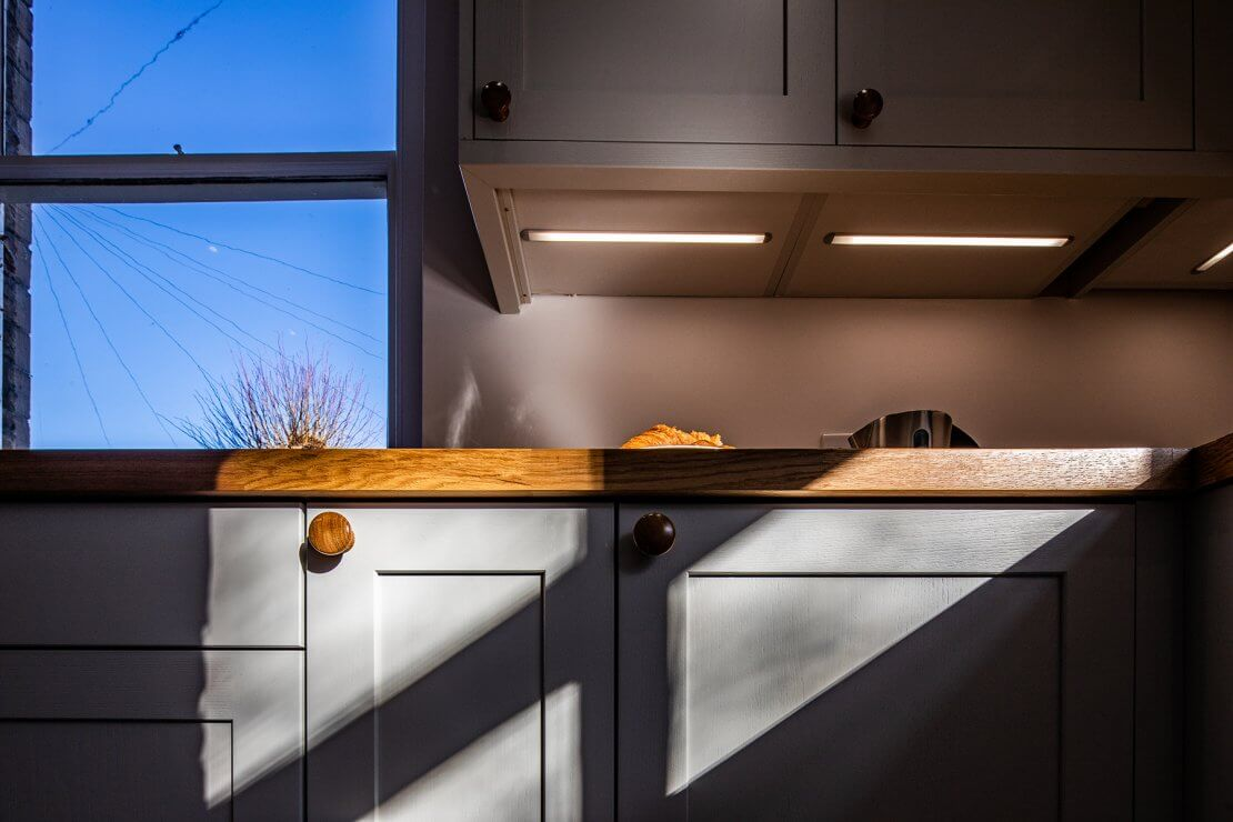 new u-shaped kitchen with shaker cabinets and oak worktop and under cabinet LED lighting