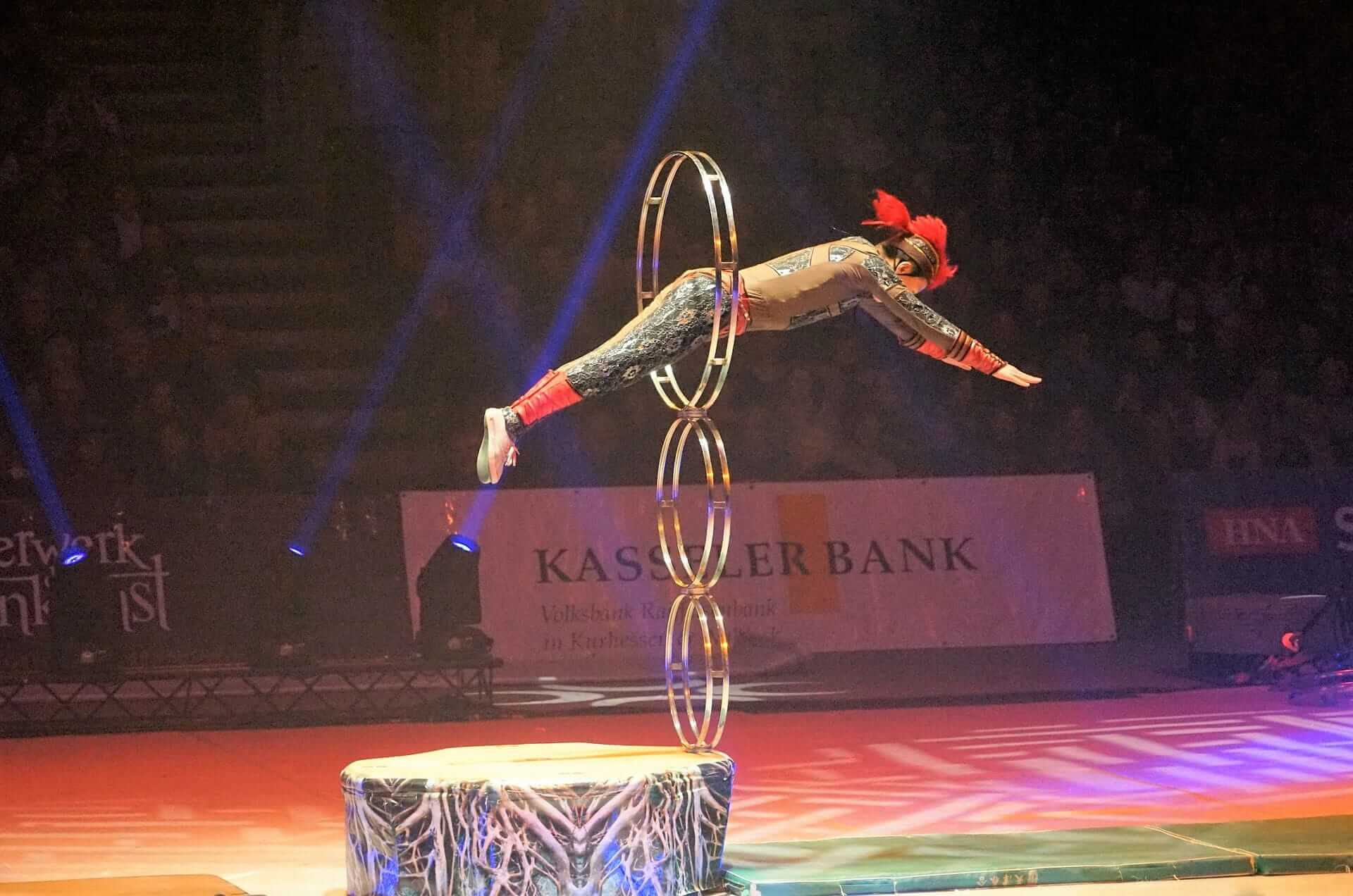 Atleta in costume che salta dentro un cerchio durante uno spettacolo.